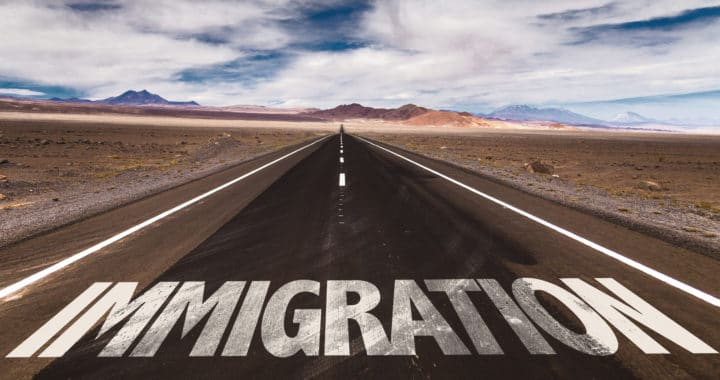 the word Immigration written on the road in the middle of the desert