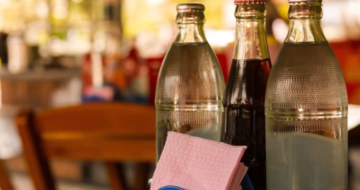 three glass soda bottles on a restaurant table