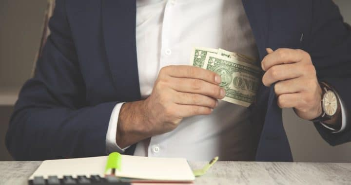 a man putting a few dollar bills into his blazer pocket