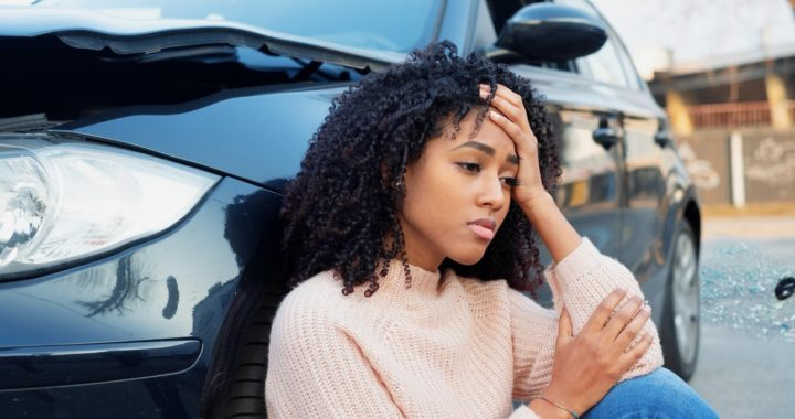 A young woman sitting next to her car after a car accident